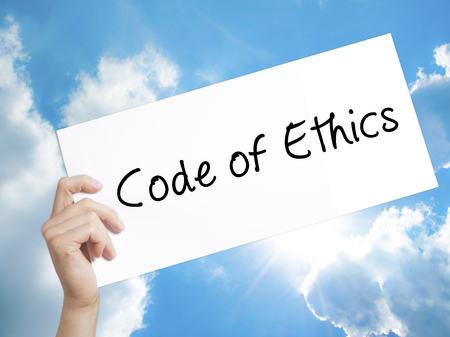 honorable: Man Hand Holding Paper with text Code of Ethics . Sign on white paper. Isolated on Sky background.  Business concept. Stock Photo