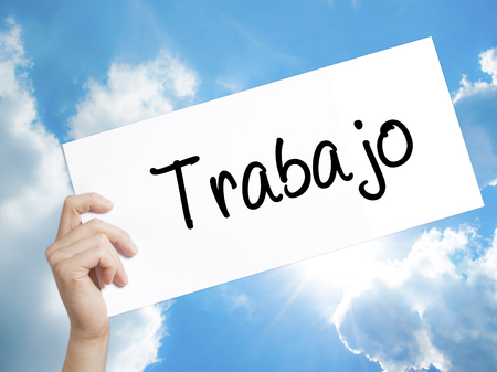 Man Hand Holding Paper with text Trabajo  ( work in Spanish) . Sign on white paper. Isolated on Sky background.  Business concept. Stock Photo Stock Photo