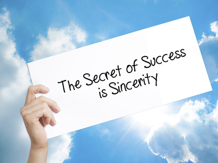 morals: Man Hand Holding Paper with text The Secret of Success is Sincerity . Sign on white paper. Isolated on Sky background.  Business concept. Stock Photo