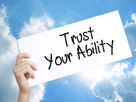 capability: Man Hand Holding Paper with text Trust Your Ability  . Sign on white paper. Isolated on Sky background.   Business concept. Stock Photo