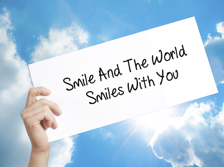 Man Hand Holding Paper with text Smile And The World Smiles To You . Sign on white paper. Isolated on Sky background.   Business concept. Stock Photo