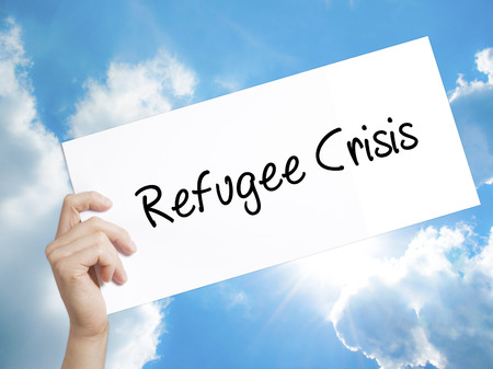 syrian civil war: Man Hand Holding Paper with text Refugee Crisis . Sign on white paper. Isolated on Sky background.  Business concept. Stock Photo