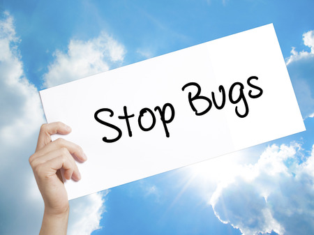pest control: Man Hand Holding Paper with text Stop Bugs . Sign on white paper. Isolated on Sky background.  Business concept. Stock Photo Stock Photo