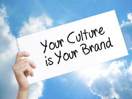 identidad cultural: Mano del hombre que sostiene el papel con el texto su cultura es su marca de fábrica. Firme en el Libro Blanco. Aislado en el cielo de fondo. Concepto de negocio. Foto de stock