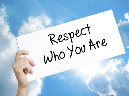 Man Hand Holding Paper with text Respect Who You Are . Sign on white paper. Isolated on Sky background.  Business concept. Stock Photo