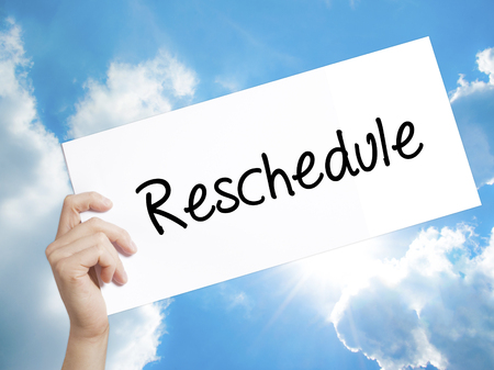 rescheduling: Man Hand Holding Paper with text Reschedule  . Sign on white paper. Isolated on Sky background.  Business concept. Stock Photo Stock Photo