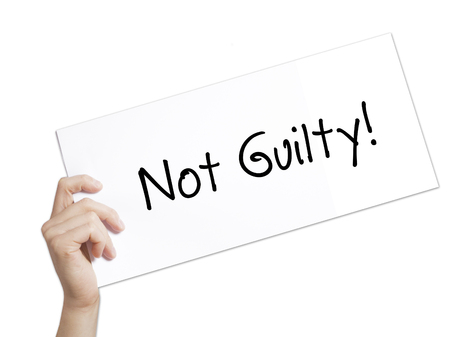 white backing: Paper with text NOT GUILTY . Man Hand Holding Sign on white paper. Isolated on white background.  Business concept. Stock Photo Stock Photo