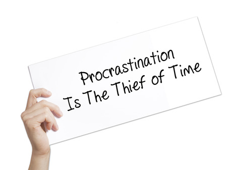 Paper with text  Procrastination Is The Thief of Time . Man Hand Holding Sign on white paper. Isolated on white background.  Business concept. Stock Photo