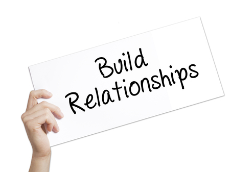 Paper with text Build Relationships . Man Hand Holding Sign on white paper. Isolated on white background.  Business concept. Stock Photo