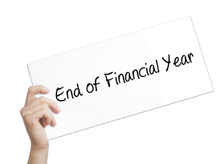 End of Financial Year Sign on white paper. Man Hand Holding Paper with text. Isolated on white background.  Business concept. Stock Photo Stock Photo