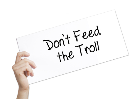 instigator: Dont Feed the Troll Sign on white paper. Man Hand Holding Paper with text. Isolated on white background.  Business concept. Stock Photo Stock Photo