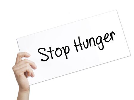 dearth: Stop Hunger Sign on white paper. Man Hand Holding Paper with text. Isolated on white background.  Business concept. Stock Photo