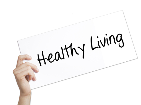 Healthy Living  Sign on white paper. Man Hand Holding Paper with text. Isolated on white background.  Business concept. Stock Photo