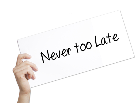 Never too Late Sign on white paper. Man Hand Holding Paper with text. Isolated on white background.  technology, internet concept. Фото со стока