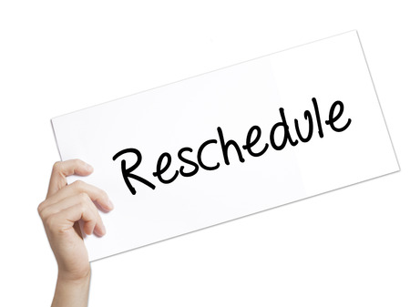 rescheduling: Reschedule  Sign on white paper. Man Hand Holding Paper with text. Isolated on white background.  Business concept. Stock Photo