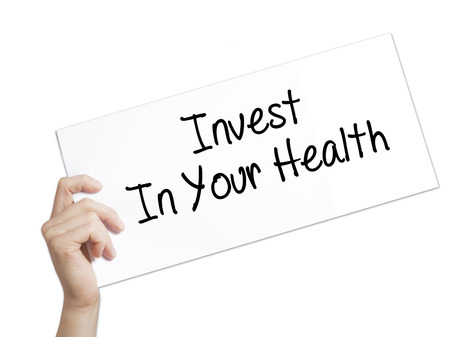 Invest In Your Health Sign on white paper. Man Hand Holding Paper with text. Isolated on white background.  Business concept. Stock Photo