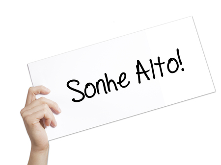 Sonhe Alto! (Dream Big in Portuguese) Sign on white paper. Man Hand Holding Paper with text. Isolated on white background. Business concept. Stock Photo Imagens