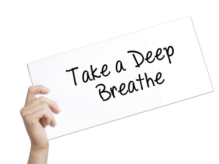 Take a Deep Breathe Sign on white paper. Man Hand Holding Paper with text. Isolated on white background.   Business concept. Stock Photo