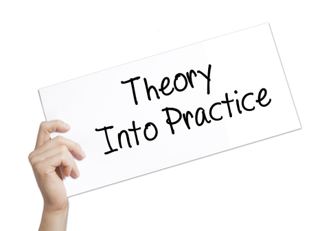 Theory Into Practice Sign on white paper. Man Hand Holding Paper with text. Isolated on white background.   Business concept. Stock Photo