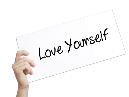 selfish: Love Yourself Sign on white paper. Man Hand Holding Paper with text. Isolated on white background.   Business concept. Stock Photo