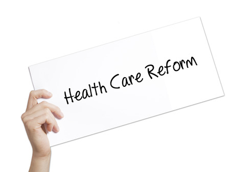 Health Care Reform Sign on white paper. Man Hand Holding Paper with text. Isolated on white background.  technology, internet concept.