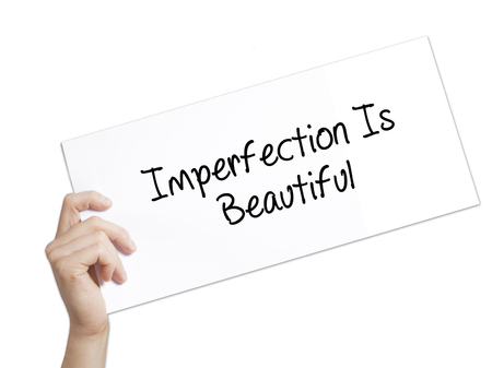 perfectionist: Imperfection Is Beautiful Sign on white paper. Man Hand Holding Paper with text. Isolated on white background.  Business concept. Stock Photo