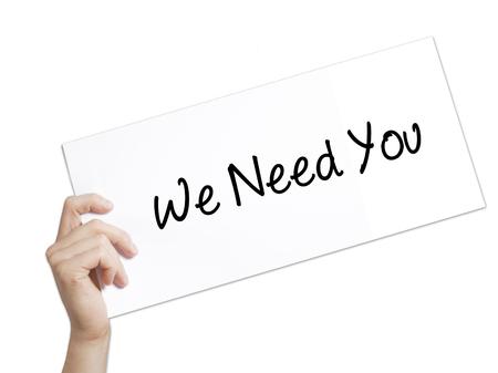 We Need You Sign on white paper. Man Hand met papier met tekst. Geïsoleerd op witte achtergrond Bedrijfsconcept. Stock foto Stockfoto