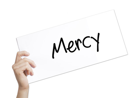 Mercy Sign on white paper. Man Hand Holding Paper with text. Isolated on white background.   Business concept. Stock Photo Stock Photo