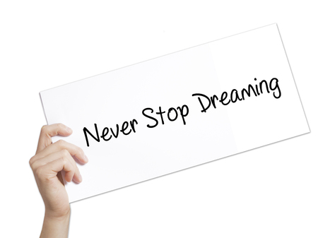 Never Stop Dreaming Sign on white paper. Man Hand Holding Paper with text. Isolated on white background.   Business concept. Stock Photo