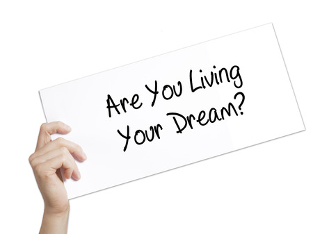 living wisdom: Paper with text Are You Living Your Dream? . Man Hand Holding Sign on white paper. Isolated on white background.   Business concept. Stock Photo