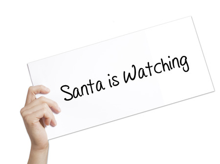 Santa is Watching Sign on white paper. Man Hand Holding Paper with text. Isolated on white background.   internet concept. Stock Photo Stock Photo