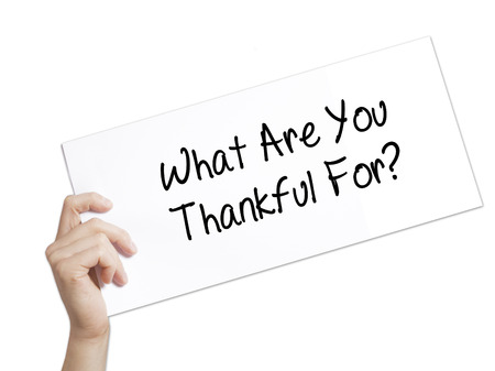 humility: What Are You Thankful For? Sign on white paper. Man Hand Holding Paper with text. Isolated on white background.  technology, internet concept.