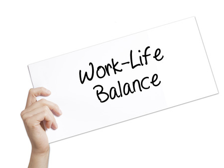 health equity: Work-Life Balance Sign on white paper. Man Hand Holding Paper with text. Isolated on white background.   Business concept. Stock Photo