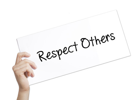 Respect Others Sign on white paper. Man Hand Holding Paper with text. Isolated on white background.   Business concept. Stock Photo