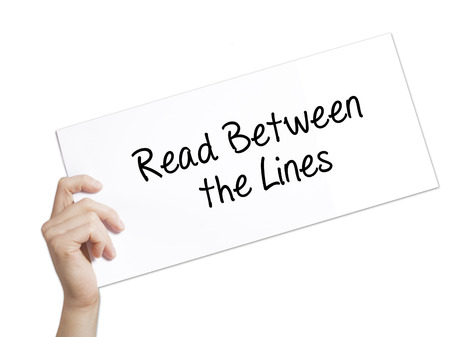 Read Between the Lines   Sign on white paper. Man Hand Holding Paper with text. Isolated on white background.   Business concept. Stock Photo