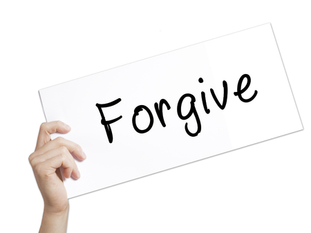redeeming: Forgive Sign on white paper. Man Hand Holding Paper with text. Isolated on white background.  Business concept. Stock Photo