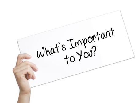Co jest dla Ciebie ważne? Zarejestruj się na białym papierze. Mężczyzna ręka trzyma papier z tekstem. Pojedynczo na białym tle. Pomysł na biznes. Zdjęcie seryjne