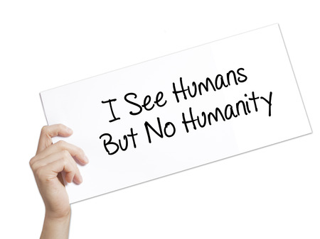 I See Humans But No Humanity Sign on white paper. Man Hand Holding Paper with text. Isolated on white background. Isolated on background. Business, technology, internet concept. Stock  Photo