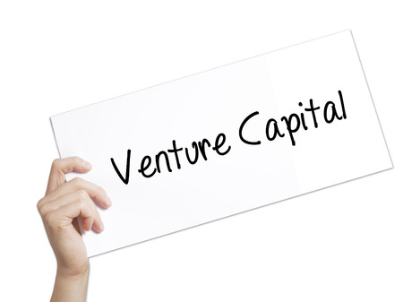 Venture Capital Sign on white paper. Man Hand Holding Paper with text. Isolated on white background.   Business concept. Stock Photo