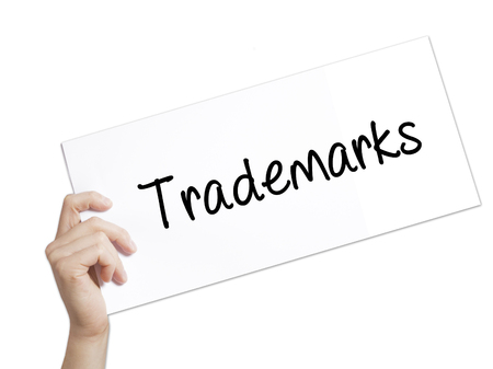 Trademarks  Sign on white paper. Man Hand Holding Paper with text. Isolated on white background.  Business concept. Stock Photo