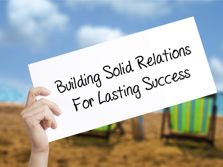 Building Solid Relations For Lasting Success Sign on white paper. Man Hand Holding Paper with text. Isolated on holiday background.  Business concept. Stock Photo Фото со стока