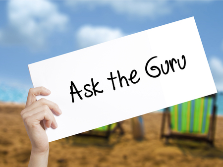 stock market launch: Ask the Guru Sign on white paper. Man Hand Holding Paper with text. Isolated on holiday background.   Business concept. Stock Photo Stock Photo