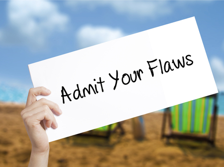 Admit Your Flaws Sign on white paper. Man Hand Holding Paper with text. Isolated on holiday background.  Business concept. Stock Photo