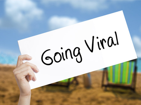 newest: Going Viral Sign on white paper. Man Hand Holding Paper with text. Isolated on holiday background.  Business concept. Stock Photo Stock Photo