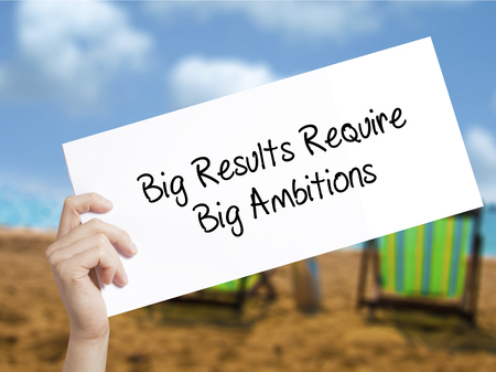 Big Results Require Big Ambitions Sign on white paper. Man Hand Holding Paper with text. Isolated on holiday background.   Business concept. Stock Photo