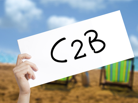 reverse: C2B Sign on white paper. Man Hand Holding Paper with text. Isolated on holiday background.  Business concept. Stock Photo