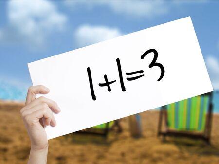 1+1=3 Sign on white paper. Man Hand Holding Paper with text. Isolated on holiday background.  Business concept. Stock Photo