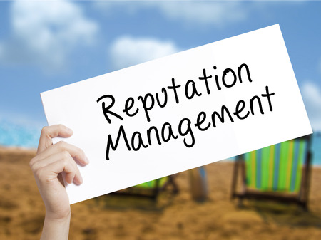 reputable: Reputation Management Sign on white paper. Man Hand Holding Paper with text. Isolated on holiday background.  Business concept. Stock Photo