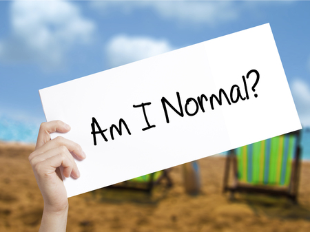 self awareness: Am I Normal? Sign on white paper. Man Hand Holding Paper with text. Isolated on holiday background.  Business concept. Stock Photo