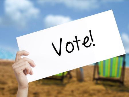 governing: Vote! Sign on white paper. Man Hand Holding Paper with text. Isolated on holiday background.   Business concept. Stock Photo
